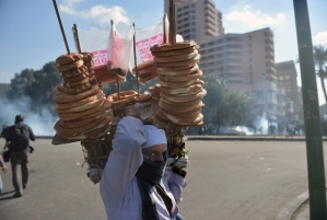 An Egyptian street vender selling bread walks past as a tear gas canister (background) fired by riot police during clashes with protesters near Cairo's Tahrir Square on January 29, 2013. Egypt's military chief warned that the political crisis sweeping the country could lead to the collapse of the state, as thousands defied curfews and the death toll from days of rioting rose to 52. AFP PHOTO / KHALED DESOUKI / AFP PHOTO / KHALED DESOUKI